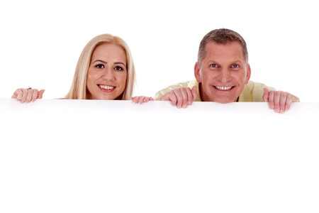 Man and woman holding empty white board and smiling at camera Stock Photo - 7368604