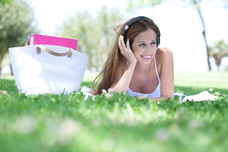 Smiling young women lying on the grass and listening music photo