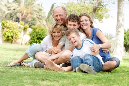 Extended group portrait of family enjoying day in park photo