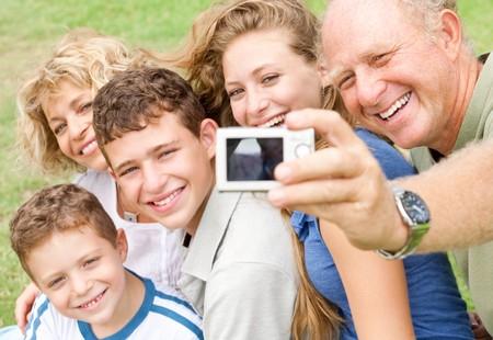 Famille heureuse de cinq sourire � la cam�ra comme grand-p�re clique sur le moment de la journ�e  Banque d'images