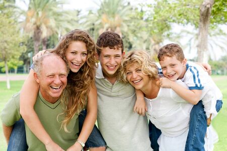 Granparents giving piggy-ride to young generation as they smile at camera