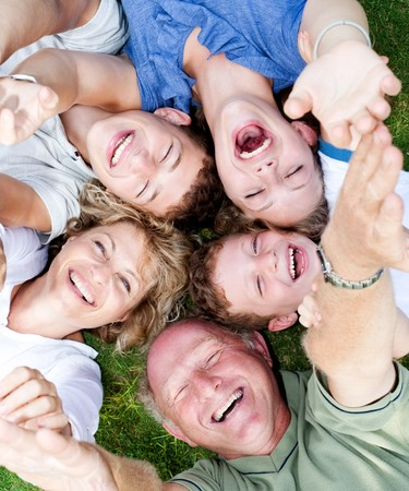 extended: Multi-generation family lying in circle and laughing at camera with raised arms Stock Photo