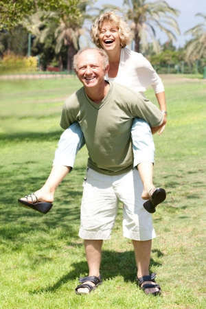 lovable: Handsome aged man gives his lovable wife piggy-ride