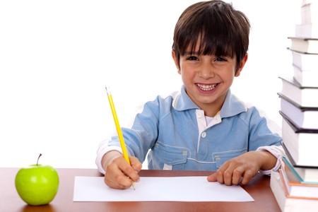 Young kid enjoying art as he draws on blank sheet of paper photo