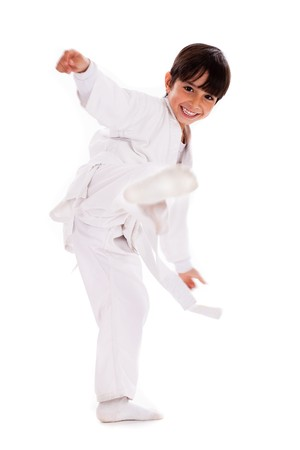 karate boy: Karate kid kicking over isolated white background