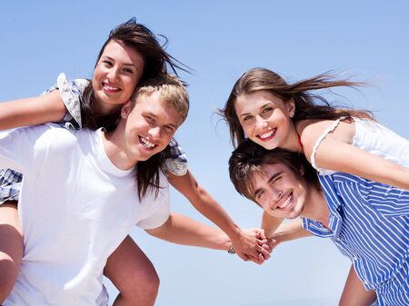 Young men giving his  women  piggy back and having fun over blue sky background Stock Photo - 7504711