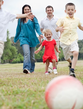 Sportive family playing football on the green lawn over natural background photo