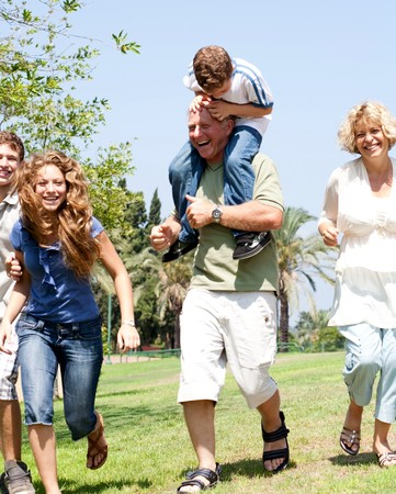 the runs: Grandson riding on grandfathers shoulders as family runs in park