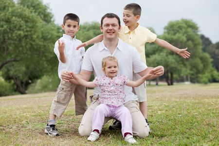 Happy family posing together on natural background looking at you photo