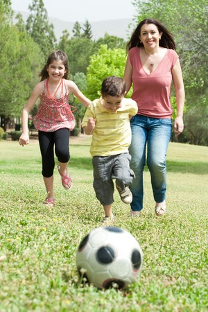women having fun: Family playing soccer and having fun, outdoor at the park Stock Photo