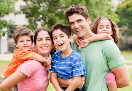Caucasian parents piggyback their children, posing outdoors Stock Photo