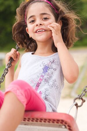Lovely girl on a swing in the park, outdoors photo