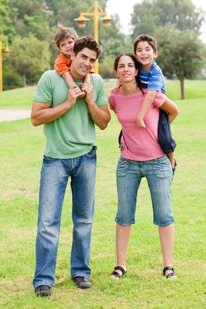 piggyback ride: Couple giving piggyback ride to their children and looking into camera Stock Photo