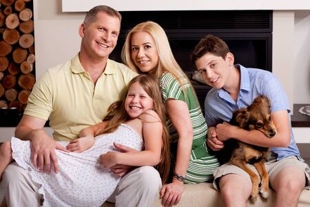 Lovable family poisng in living room as young boy holds little puppy in his arms photo