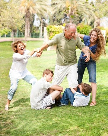 Family members holding back grandfather and having fun photo