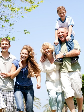 Happy family having fun in the park with three children Stock Photo