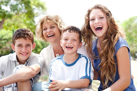 Mother with grown up daughter and son in the park smiling and having fun photo