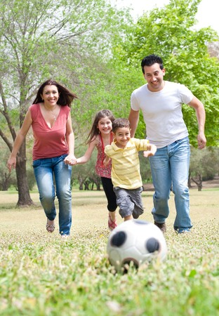 Parents and two young children playing soccer in the green field, outdoor photo