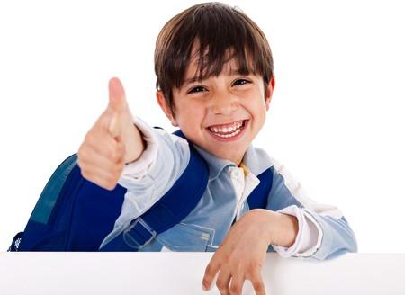 school bag: Sonriente muchacho de parvulario mostrando pulgares arriba signo como �l respalda el tablero blanco en blanco sobre fondo aislado