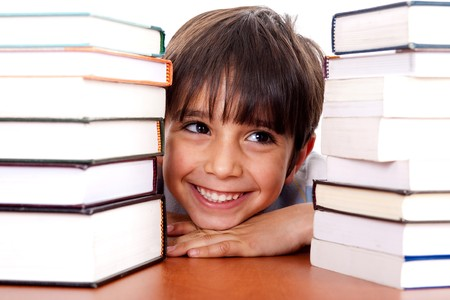 Young kid relaxing between pile of books and looking away
