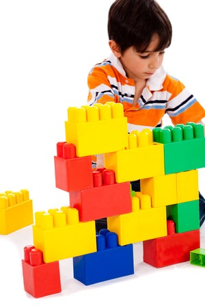 toy house: Young boy playing with building blocks on white background