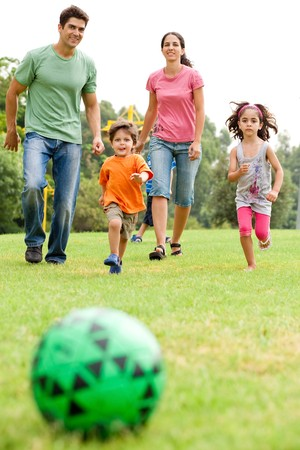 Kids run towards the football as parents follow them photo