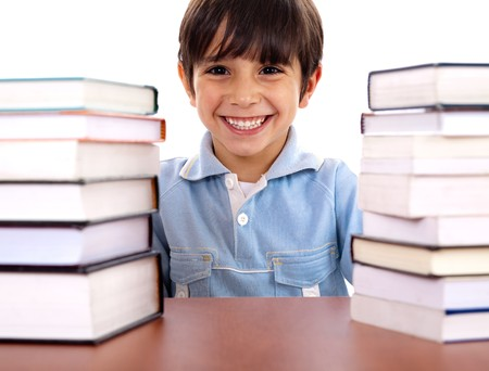 pileup: Smiling young school boy surrounded by books on white background