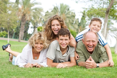 Multi-generation family enjoying sunny day in park and having fun photo