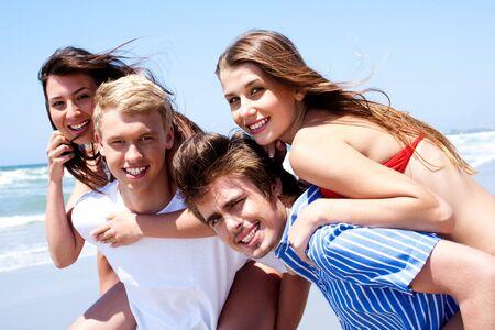 Young women enjoying piggyback ride by the beach photo