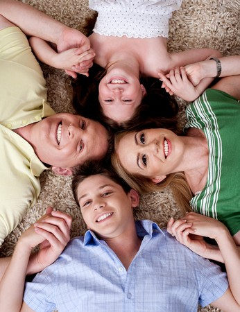 Happy family of four lying on the carpet and holding each others hand, looking at camera photo