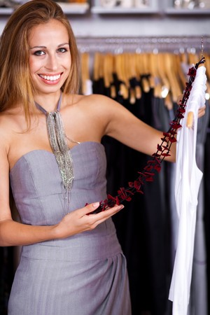 Gorgeous woman in wardrobe store picking her choice photo