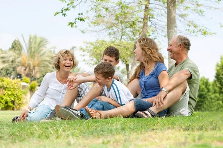 Portrait of extended family relaxing on sunny day in park and having good time photo