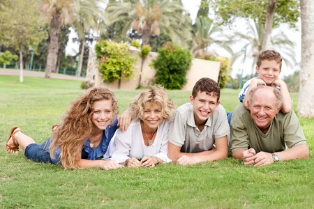 Portrait of a happy family lying down on the green grass in park photo
