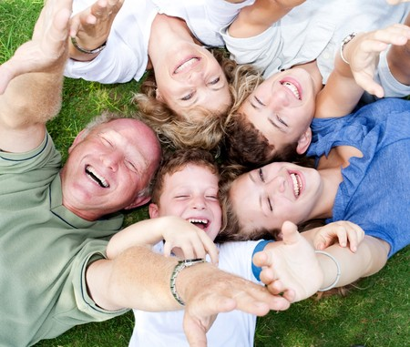Happy family lying as a circle in the park and raising their hands photo