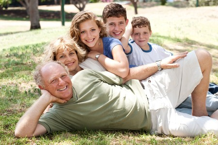 Three generation Caucasian family lying on green grass in the park smiling. photo