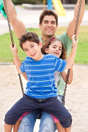 Father and children enjoying swing ride on a sunny day photo