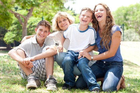 front view of happy family sitting in park and posing for camera photo