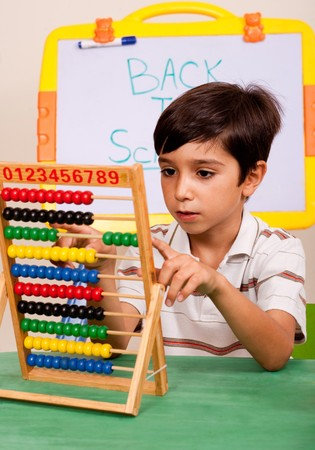 Young boy playing abacus in classroom enviroment photo