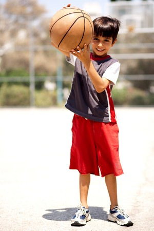 Adorable boy with basketball, outdoors