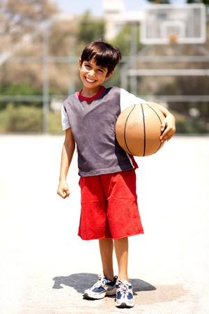 Adorable boy with basketball, outdoors photo