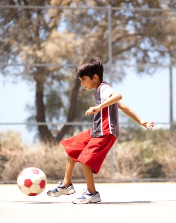 Young kid in action enjoying soccer, outdoors Stockfoto