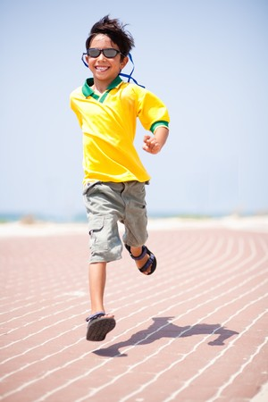 Young kid running on race track and enjoying himself