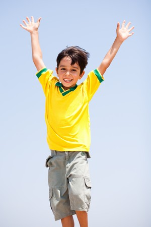 Young kid with raised arms posing in front of camera photo
