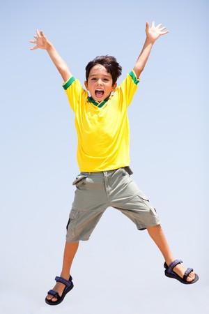 persona saltando: Smart kid salto alto en el aire, brazos estirados y mirando a la c�mara Foto de archivo
