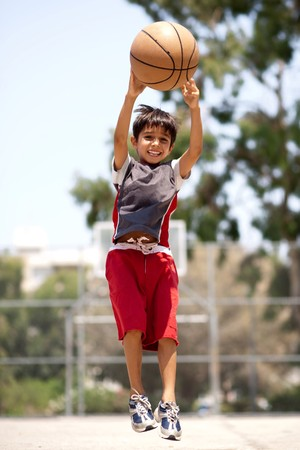 Young basketball player jumping high in air as he throws the ball Stock Photo