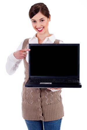 portrait of woman holding laptop and pointing  at it against an isolated background photo