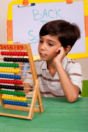 A student solving a math assignment using an abacus photo