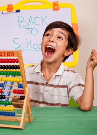 Boy with abacus screaming loudly in classroom enviroment photo