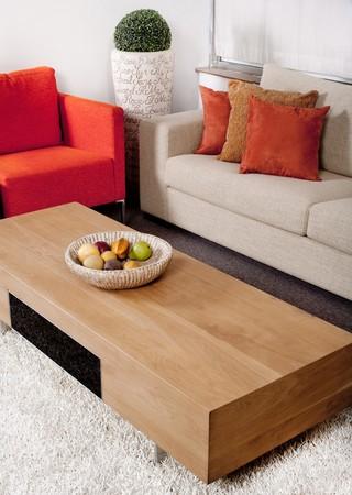muebles de madera: Sala de estar con el sof�s cl�sicos y mesa de madera con frutas artificiales en la cesta  Foto de archivo