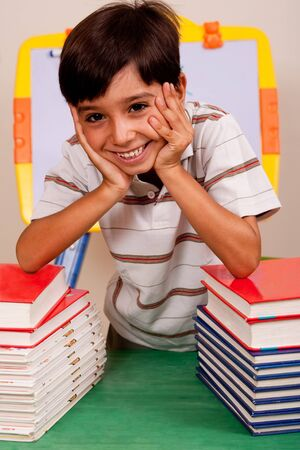leaned: Young boy leaned over pile of books Stock Photo